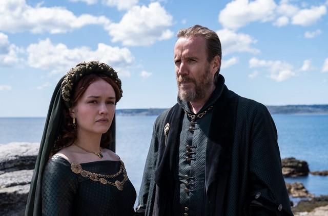 """Die zweite (und aktuelle) Gattin des Königs: Alicent Hightower (Olivia Cooke) mit ihrem Vater Otto Hightower (Rhys Ifans) - der als """"Hand des Königs"""" im Zentrum der Macht sitzt und seiner Tochter schon in jungen Jahren politisches Geschick vermittelte."""