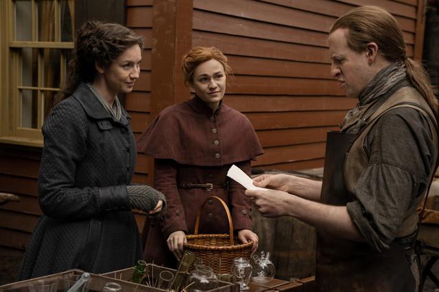 Claire (Caitriona Balfe) und Brianna (Sophie Skelton) geben bei einem Glasbläser das Gehäuse für eine Spritze in Auftrag.