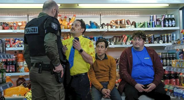 """Das Chaos ist komplett: Georg (Stefan Haschke, M.) mit Ketchup-Flecken übersäht, Daniel (Ludwig Trepte, l.) und Olaf (Daniel Zillmann, r.) sind fertig mit den Nerven und die Polizei hat gerade eine """"Geiselnahme"""" beendet, die kein war..."""