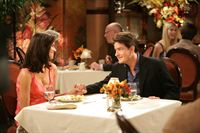 """Charlie (Charlie Sheen, r.)  will seiner Freundin Chelsea (Jennifer Bini Taylor, l.) bei einem Glas Champagner einen Heiratsantrag  machen, um ihr so die begehrten drei Worte zu entlocken. Das mit dem """"Ich liebe dich"""" klappt. Doch die Sache mit dem Verlobungsring endet komplizierter als er es sich vorgestellt hat..."""